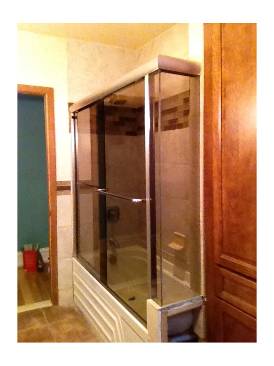 Sliders - Frameless tub sliber with a small return in bronze glass. Both doors slides. Comes with towel bar and knob. by John Tallarida