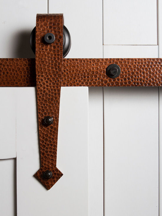 "Barn Door Hardware - A perfect combination of rustic design and old world ""blacksmithing"" techniques, this Hammered Arrow roller hanger is defined by its hand hammered texture and pointed arrowhead base. The Hammered Arrow roller hanger is designed with a rounded top edge, leaving the wheel exposed and visible as it rolls along the track. This hanger mounts the face of the door."