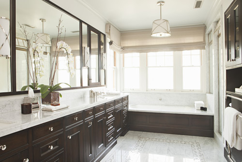 Bathroom with a white and brown counter and a ceiling light right above the tub