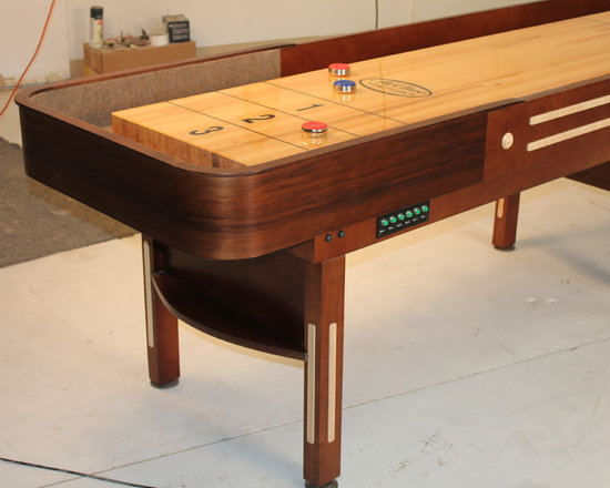 Prestige Shuffleboard Table - The Prestige shuffleboard table is a classic shuffleboard model and makes the perfect furniture for a transformed garage or man cave. Made using American walnut and hard maple wood, the Prestige is reminiscent of the original American shuffleboard table design from the late 1940s. The table starts with a true horse collar made from a single piece of wood strengthened with several layers. We then steam-bend them with a final layer of solid American walnut wood. The cabinet and legs are made from solid select Michigan maple, and the trim also comes from all-American walnut in order to bring out the table's natural beauty. We offer the Prestige shuffleboard table in a beautiful natural or Cognac finish, to further bring out the contrasting tones of the American maple and natural walnut wood.