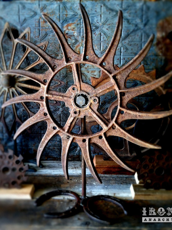 """Antique Industrial Gear Decor - Extra-terrifying old wheel with angry, curved claws of thick iron. Crusty, rusty patina to ensure you know it means business! Custom display stand with horseshoe base allows wheel to spin. 19.5"""" diameter."""