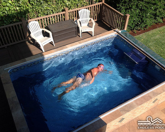 Backyard Deck Endless Pool® - Even with limited deck space, an Endless Pool can revitalize a backyard. In this installation, the pool is skirted with softly marbleized tiles for an organic integration with the deck and plant life.