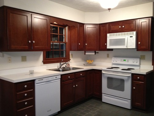 Brown cabinets white corian countertop w white appliances for Brown kitchen cabinets with black appliances