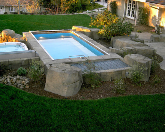 Original Endless Pools® - The perfect pool for your modern stone-age family! Surrounded by boulders and a matching tile perimeter, this Endless Pool installation contrasts a quarry-like feel against the lush, expansive lawn.