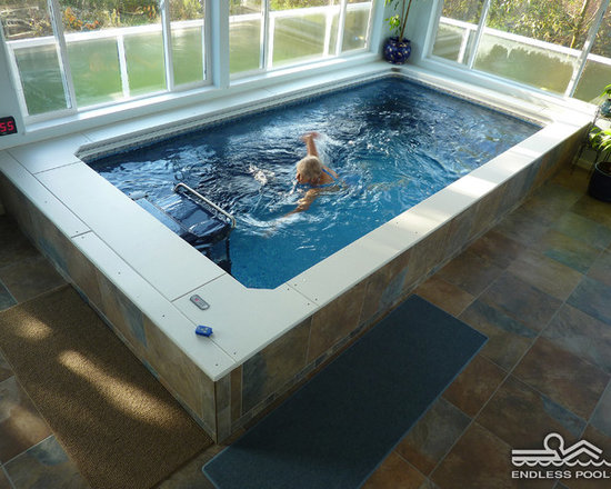 Indoor Endless Pool® - In this sunroom installation, the Endless Pool provides year-round exercise and recreation. Frosted glass on the lower windows provides privacy while still permitting plenty of natural light. The tile's rich rust and slate tones add to the warmth.