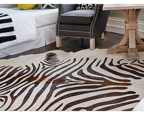 Stenciled Zebra Cowhide Rug - With a brown zebra pattern stenciled on a light beige hide, our Zebra Cowhide Rug makes a sophisticated, rustic focal point. With textural interest and handsome looks, this hand-finished, natural cowhide rug is one of the finest quality hides on the market and a timeless addition to any room in the house.