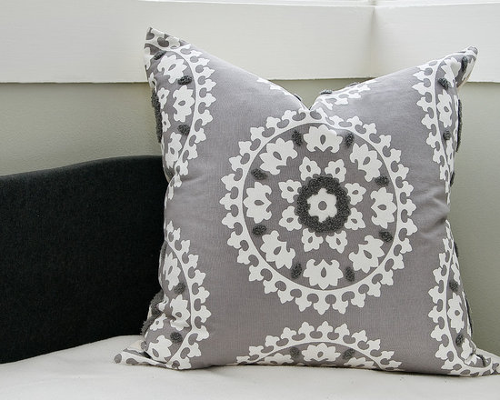 Gray Suzani Pillow - This Suzani print pillow, backed with gorgeous gray and white canvas, transports us to the Middle East while retaining a bit of a contemporary edge. Embellished with hooked embroidery, it has a tactile quality that we can't help but cozy up to. Made in the USA. Shown in Gray (not available). Available in Blue.