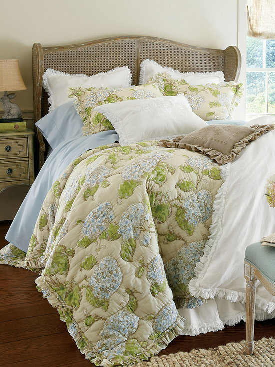 Hamptons Quilt - A touch of summer in the Hamptons for the bed, our simple yet elegant collection is patterned after a hand-painted watercolor original from the late 19th century. Lacey hydrangea blossoms are dappled in soft shades of periwinkle blue and fresh green on a tea-stained ground. Printed on airy cotton voile, hand-stitching outlines each flower and leaf, creating rich textural dimension. A gathered ruffle border with purposely frayed edges and inset washed velvet ribbon gives this original quilt the look and feel of an heirloom find. The bed sham (sold separately) is unquilted and features a hidden zip closure. Each sold separately