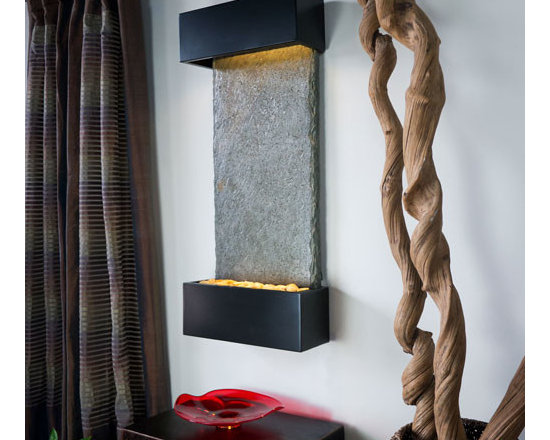 Bluworld - Verdigris Falls Vertical Lightweight Slate Fountain - Black Onyx Trim - Modern and sleek, the Verdigris Slate glistens with Mica making it sparkle under the gentle sheeting water. The semi-matte Black Onyx Trim compliments the fountain's modern aesthetic. The vertical fountain panel is made of genuine slate bonded with a composite material for an extremely lightweight design that can be installed in 30 minutes or less. Water gently flows down the Verdigris slate face into a basin filled with polished river rocks. Easily adjust the flow of water with the included flow valve. The dimmable, remote controlled LED lighting highlights the soft cascade of water creating a dramatic focal point in any room or office.Verdigris Vertical includes long-lasting super bright white LED lights rated for over 10,000 hours of use and an ergonomic finger slide remote control to easily dim or brighten the LED lights or turn them on and off. This water fountain glistens as water sheets over the genuine Indian Slate flowing passed polished river rock creating a soothing sound and beautiful focal point for any room. This fountain is engineered with Bluworld's clog-free, splash-free design and features the Water Wonders NSI�� genuine light weight Slate. Installation is super easy with the lightweight nature of the NSI�� slate panels. Simply hang on the wall per the instructions. Once it's installed, your only concerns are setting the flow rate and turning on the accent light with your handy remote.This water fountain can be customized with your logo. Etched and hand-painted logos start at only $395.00. Contact our sales department for more information at 1-888-499-5433.Free freight is only available in the 48 Contiguous United States. Please contact us so that we can provide you with a quote when shipping to Alaska, Hawaii, other US territories or international.