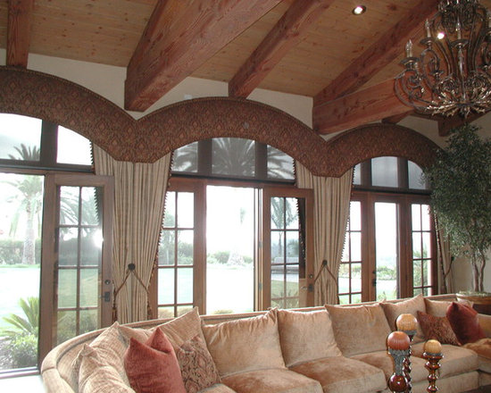 Top Treatments - Shaped cornice boxes with decorative nail head accents made to match curvature of windows and clear the open beams, mounted over motorized roller shades and stationary drapery tie-backs.