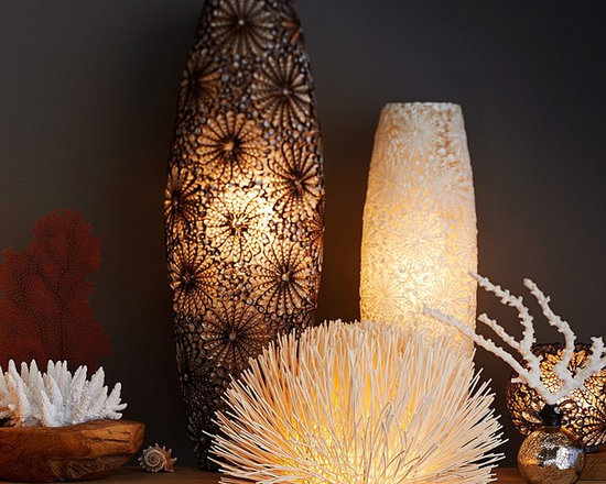 KAI SHELL AMBIENT CYLINDER TABLE LAMPS - Like treasures from the sea, each of these lamps is one of a kind. Artisans create their intricate botanical designs by cutting and placing hundreds of small shells on a resin base. When the lamps are switched on, the light illuminates their lacy filigree and emits a mood-setting glow.