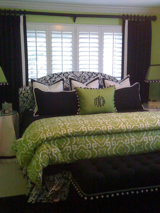 Green Bedroom - Stationary black side panels with a lead edge trim frame this spectacular ensemble of bedding and pillows absolutely perfectly.  Design by Calico Corners.  Installation by Curtain Pros.