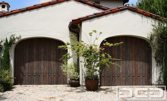 Spanish Style Garage Door | Handcrafted in Reclaimed Wood & Rustic Iron Clavos mediterranean garage and shed
