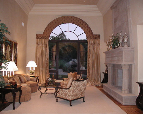 Top Treatments - Shaped cornice box to fit contour of arched window with decorative nail heads and medallion mounted embroidered silk taffeta stationary side panels puddled at the floor.