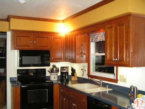 cinnamon color of the oak cabinets to disguise or blend the soffits