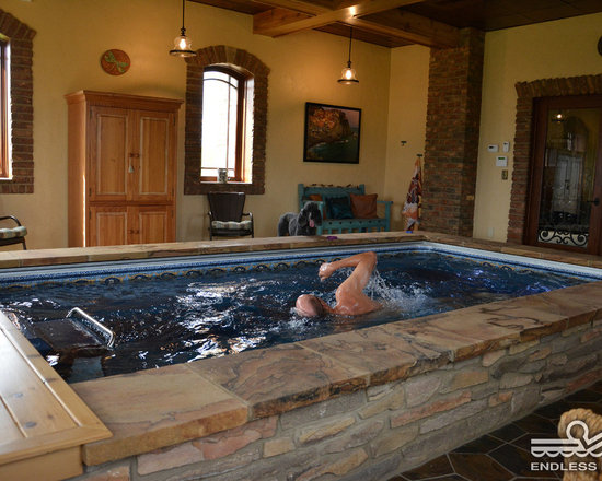 Indoor Endless Pool® - Arched windows, brick accents, and rich ochre walls bring a bit of Tuscany to this pool room. The modular Endless Pool, here finished with marble tile and multicolored stone, can be easily assembled in existing spaces.