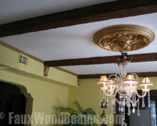 Faux Timber Beams - Faux wood beams in a timber finish create a crisscross ceiling beam pattern, accented with corbels, to decorate this kitchen and match the wood cabinets.