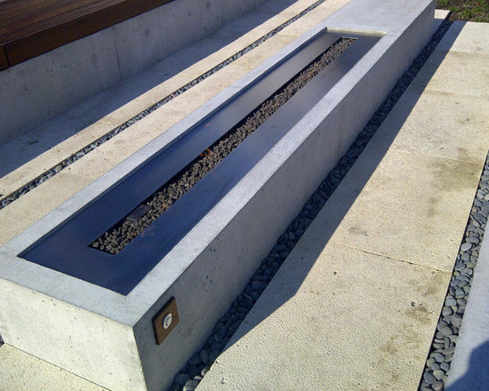 Concreate Outdoor Fireplace - VGF Custom Fireplace team was asked to provide a linear stainless steel burner approximately eight feet long for a custom house project in West Vancouver.  Both the linear burner and the ignition module were designed to fit into the cement bed.