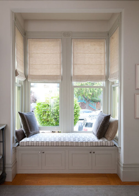 Motorized Roman Shades in a bay window and built in window seat traditional roman blinds