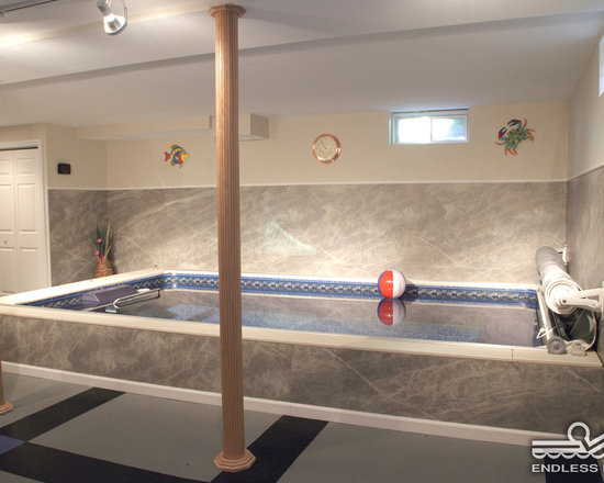 Indoor Basement Endless Pools® - This renovated basement gets some unexpected functionality with an Endless Pool. Its modular design allows all parts to fit through doorways and down stairs. The softer tones make the most of the limited natural light.