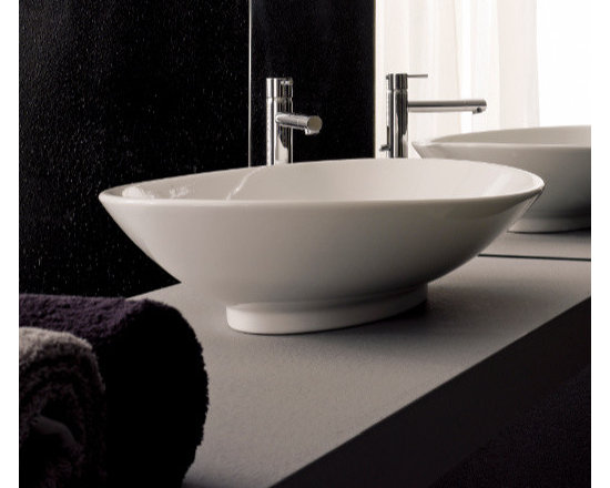 "Scarabeo - Decorative Oval Shaped Contemporary Vessel Sink by Scarabeo - Decorative oval shaped contemporary bathroom sink designed and manufactured in Italy by Scarabeo. Made of high quality white ceramic. Round above counter vessel sink comes without overflow and has no option for faucet holes. Sink dimensions: 25.00"" (width), 5.80"" (height), 18.10"" (depth)"
