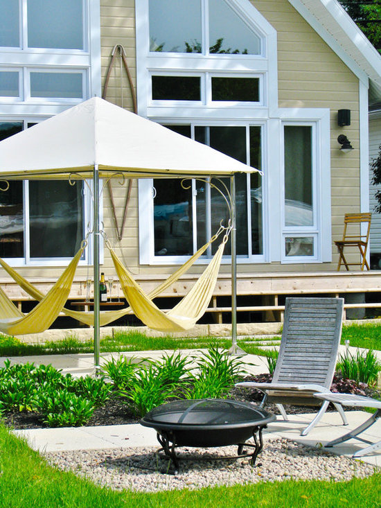 Eternity Hammock by Trinity Hammocks - The Infinity Hammock is a modern twist on the outdoor hammock with its three ring design. The hammocks themselves are available in two styles: quilted or woven. The quilted hammocks are ideal for a more comfortable lounging experience where moisture is not prevalent. They should be stored in a dry space during the night or rainfall. The woven hammocks are perfect for warmer climates and where wet bodies may want a place to lounge and dry off. They can stay outdoors year round. A teak table is suspended in the middle of the frame as a convenient surface for whatever accompanies your relaxation time. This hammock is great for yards, decks, patios and the poolside-wherever you want to enjoy the gentle cradle of this fantastic hammock.