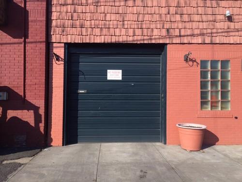 Black commercial garage door in need of upgrade.