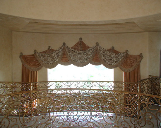 Top Treatments - Swags and stationary side panels mounted on decorative wrought iron medallions.