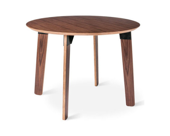 Gus - Sudbury Round Table, Walnut - The Sudbury Table is a study in contrasts. Organic forms joined together by industrial fittings. Warm wood grain stands out against sleek steel. Scaled for smaller spaces, this table's rounded shapes create a relaxed vibe that's perfect for a modern dining area. It features exposed ply legs and beveled tabletop with fittings made from durable, powder-coated steel. Available in walnut with black brackets, or natural oak with white.