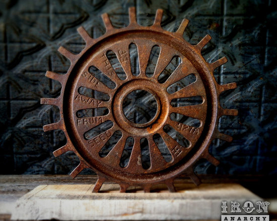 """Antique Industrial Gear Decor - Fantastic old gear of thick rusty cast iron in a hardcore industrial design. Engraved text to make it even more intriguing! Reclaimed lumber display stand. 7 5/8"""" diameter."""