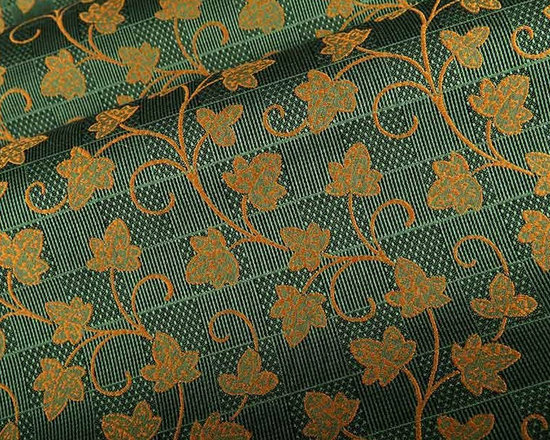 Ivy Cottage Upholstery Fabric in Green - A golden floral pattern weaves its way through this check patterned cotton blend upholstery fabric in green. Perfect for chairs, seats, or sofas or for creating classic throw pillows. Made in Switzerland from a blend of 86% cotton and 14% polyester. Width: 68″; Repeat: L:12″