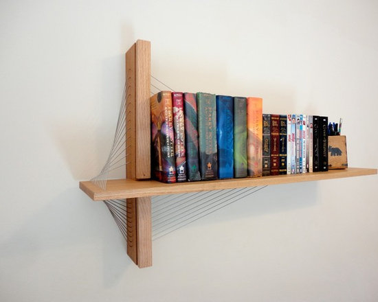 Suspension Shelf - This suspension bridge-inspired shelf is a great modern addition to any room. A sculptural piece in its own right, the shelf is especially great for those who want to be economical with their floor space. A vertical mahogany fin mounts to the wall while the red oak shelf floats one inch out. The shelf is cantilevered out from the mahogany fin with steel cables that bear the load of books and other items while at the same time creating beautiful contours. The piece is available with the shelf on either the right (as pictured) or the left (mirror of pictured version) of the mahogany fin. Weight limit is 45 lbs, evenly distributed.