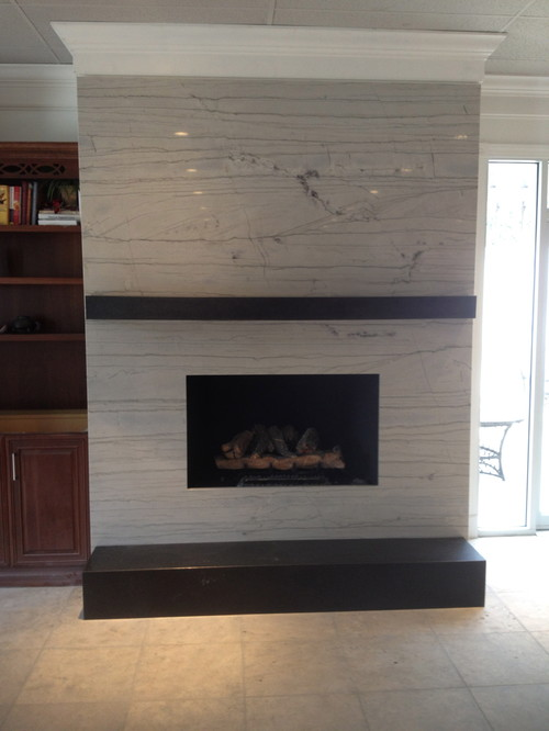 Old tired fireplace redone with granite facade, mantle and hearth