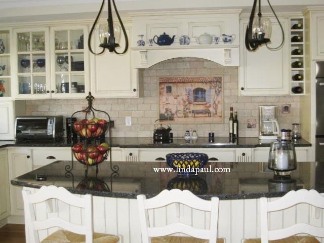 french country kitchen with white cabinets and black