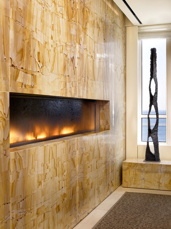 Chicago Penthouse - Fireplace water feature measuring approximately 10 1/2 ft. wide by by 1 1/2 ft. tall was custom designed for a residential penthouse in Chicago, Illinois.  The feature consists of glass and stainless steel along with the necessary components for fire and flowing water.