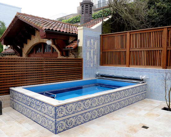 Original Endless Pools®, Patio Pool - Ornate tile in cobalt and wedgewood blues -- a striking counterpoint to the red brick and cherry wood tones, adjacent -- highlight this elegant Endless Pool. The corner installation is efficient and affords maximum privacy.