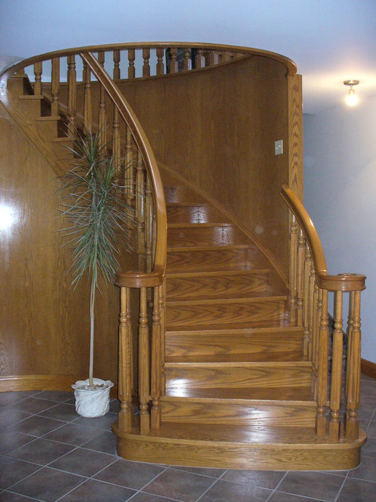 Custom Stairs - This custom wood staircase replaced a square staircase and the floor opening was adjusted to an oval, increasing the floor area above and creating a grand entry and architectural feature to the home.