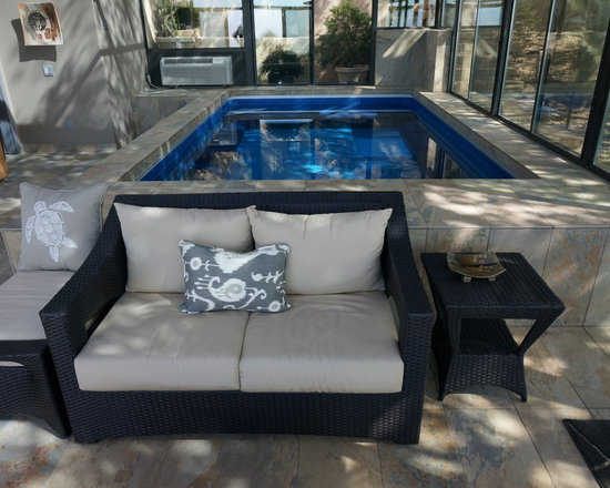 Indoor Sunroom Endless Pool® - With its quiet swim-current motor, the Endless Pool can be used for invigorating exercise while someone else curls up on the loveseat and reads! Understated marble tiles and clean neutral accents give this sunroom a timeless, welcoming air.