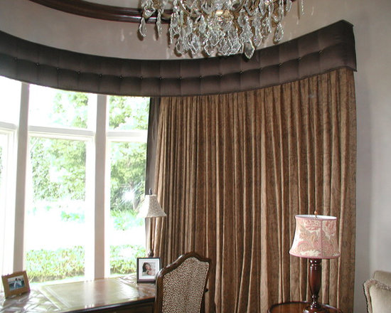 Top Treatments - Upholstered cornice box of solid colored linen fabric with decorative nail head accents, fit to curvature of room with traversing linen print draperies mounted inside. Installed on curved Kirsch Architrac hardware.