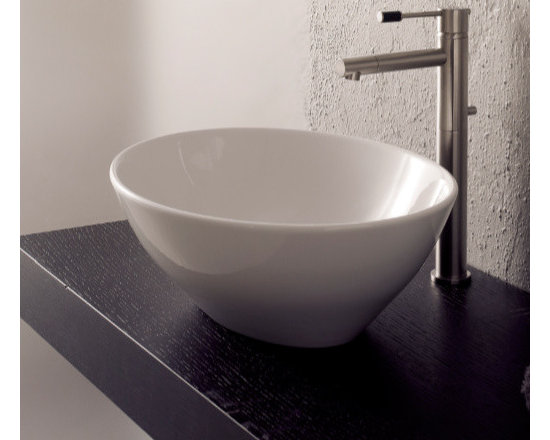 "Scarabeo - Sleek Oval-Shaped Ceramic Vessel Sink by Scarabeo - This sleek white ceramic vessel sink has an oval, bowl-shaped design perfect for modern bathrooms. It is designed without an overflow and comes with no faucet holes. Sink contains a standard drain (1.25"") and is made in Italy by Scarabeo. Sink dimensions: 16.10"" (width), 5.50"" (height), 13.40"" (depth)"