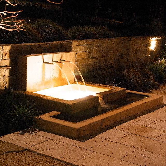 Fountain at night with stone retaining wall modern-patio