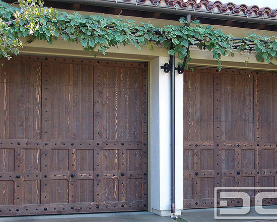 Spanish Garage Doors, Custom Designed & Handcrafted by Dynamic Garage Door of CA - Our Spanish Garage Doors are custom designed to reflect the architectural past of the colonial architecture found in Spain. Spanish Garage Doors are specifically stained by hand in a rich stain color that enhances the natural look of, in this case, the solid cedar wood. Nature's wooden grain is uniquely beautiful which accentuates the rustic look of our Spanish Garage Doors.  As the wood wood ages through exposure to the elements, time will give these doors the rustic feel of Spanish Colonial Architecture.  The garage doors will have a charming rustic look to them. Creating your own, unique Spanish Style Garage Door can be done by arranging trim pieces in diagonal, horizontal and/or vertical placements to create a stunning Spanish design such that your home will still have that Spanish style you're looking for but with a unique touch specifically designed for you!