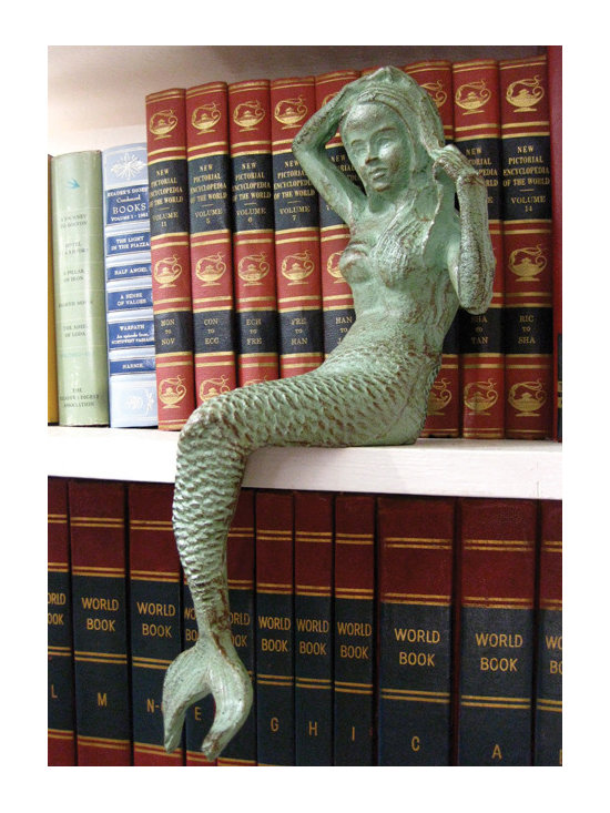 """Cast Iron Mermaid Shelf Sitter - Design is in the details! And that's why this Cast Iron Mermaid shelf sitter is the ideal decor piece for your beach home. Sitting elegantly atop your shelfs, the beautiful antique green finish will look beautiful mixed in with other patina pieces throughout your home. Dimensions: 5.5""""w x 14.5""""h"""