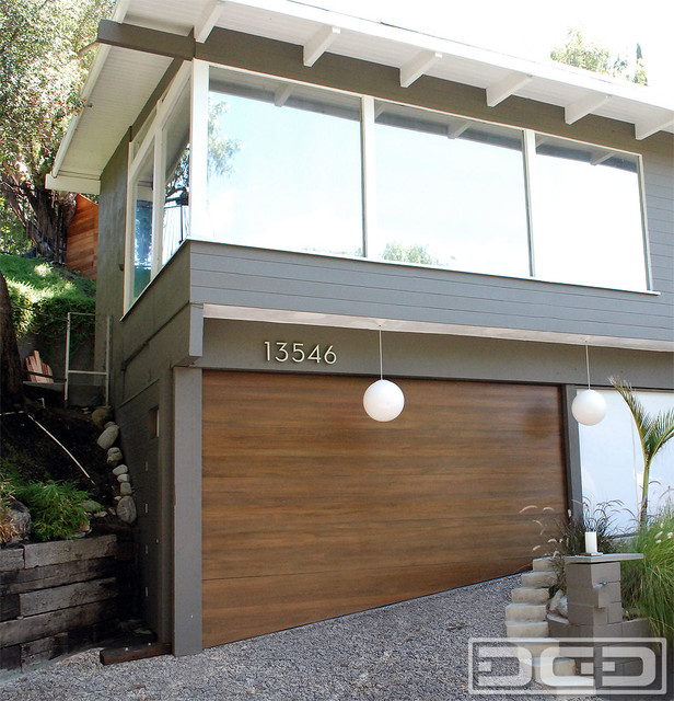 Modern garage doors with sloping bottom sections for uneven garage