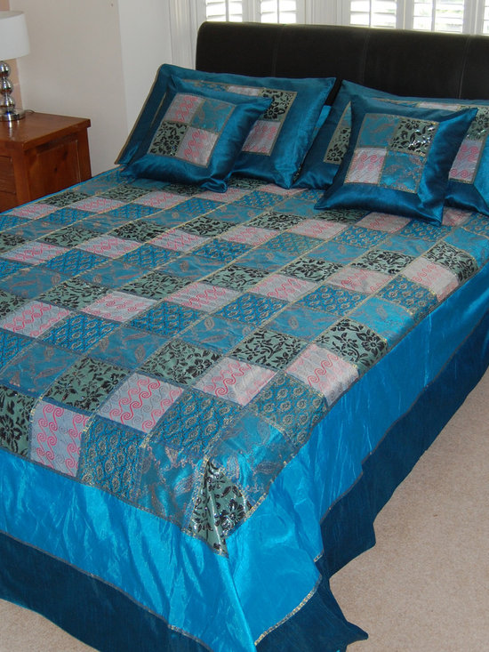 Teal Blue Indian bedspread set - Embroidered patchwork Indian bedspread set in Teal Blue. This five piece bed set has a patchwork design incorporating patches of turquoise blue paisley and pale pink swirls with a shimmering rich teal colour border. The set comprises of a bedspread, two pillowcases and two cushion covers. This truly is a stunning bedcover set.   Size 220cm x 270cm   Cushion covers 40x40cm