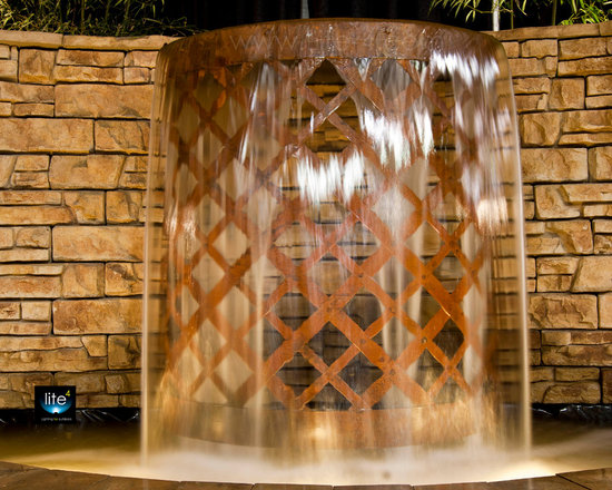Steel Fountains - This is a custom spillway fountain that I built for the 2012 local flower and patio show.  The spillway is 6' tall made of steel that has been fashioned in a basket weave pattern to match our central fountain feature.  This feature was integrated into the stone wall and creates a very unique addition to the display.  Lite4 is primarily a lighting design and installation company, however with my 20 years of experience in the landscape design and construction industry. I know also create custom water, fire and steel creations to add new dimensions to my clients' properties.