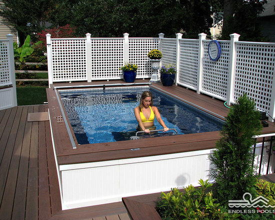 Backyard Deck Endless Pool® - A classic American backyard, updated with a partially in-ground Endless Pool. She's walking on the hydraulically powered underwater treadmill; used with or without the swim current's added resistance, it's a comfortable means to low-impact cardiovascular exercise suitable for most any fitness level.