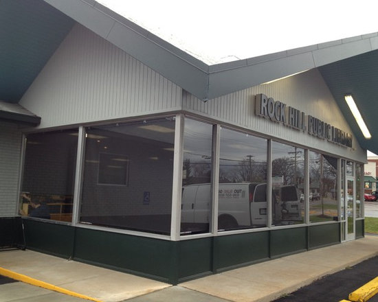 Designer Roller Shades Exterior View by Alta - Kirkwood, Mo - Two Blind Guys outfitted these large commercial windows with Roller Shades in a 5% fabric by Alta. They made a world of a difference in cutting their energy bills down. Exterior view of roller shades.