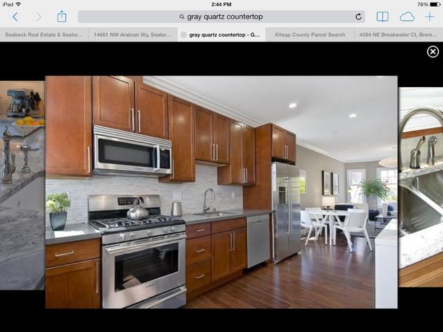 This is it! Brown shaker-style cabinets, darker floor, gray quartz countertops.