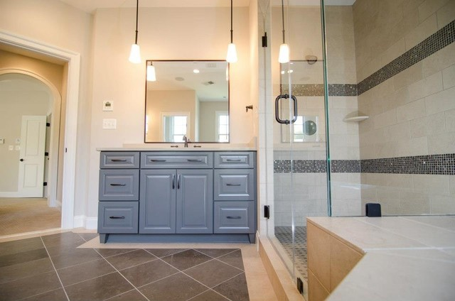 This Master Bath has two gray vanity areas.  Pendant lighting is hung in place o